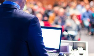 Image of the back of a man standing at a lectern in front of a conference crowd