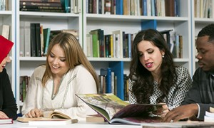 Image of four university students working together in a library