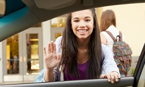 Image of a university student waving goodbye to person in car
