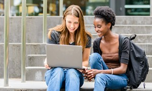 Image of students on campus steps working at laptop