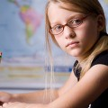 Young female student sitting at a desk in front of a world map, wearing glasses, and ho...