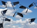 A photo of a number of graduation mortarboards tossed up in the air, against a blue sky...