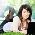 Photo of a female student laying on her stomach outside on some grass and under trees, ...
