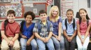 A photo of six primary school children of mixed genders and ethnicities sitting next to...