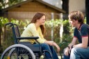 A photo of a female university student in wheelchair talking with her male friend, who ...