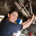 A photo of a smiling young female mechanic working on the underside of a car