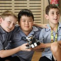 Photo of three North Lake SS primary school students sitting together on the floor and ...