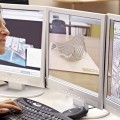 Image of a Deakin University student in front of three computer monitors, working on a ...