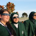 Photo of three female high school students wearing solar eclipse viewing glasses