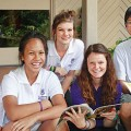 Photo of six University of Queensland students sitting on a verandah stoop, all smiling...