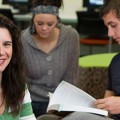 Image of three Uni SA students working together in a study space, one looking into the ...