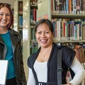 Image of two University of Tasmania students in a library, looking into the camera and ...