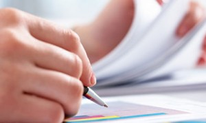 Image of a pair of hands holding a pen and flipping through reports. Evaluation.