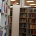 Image of a student standing in a library, looking into the camera