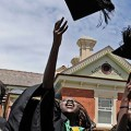 Image of young students throwing their mortarboards into the air