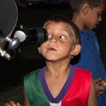 Image of a young primary school student looking into a telescope