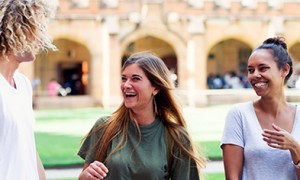 Image of three university students on campus and laughing